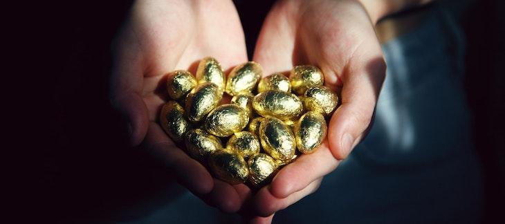 Hände mit goldenen Schokoladeeiern