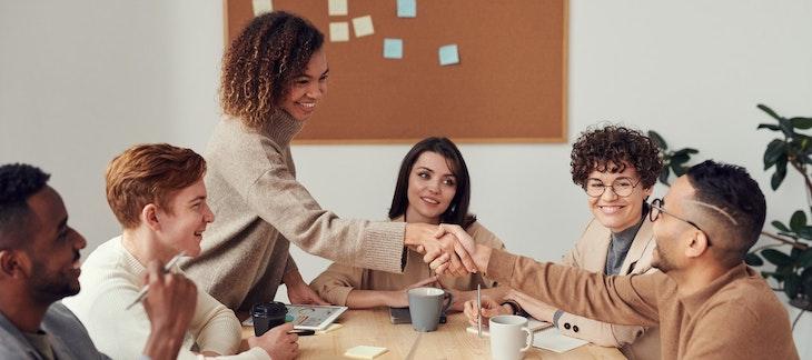 Ein Team sitzt zusammen, zwei Personen geben sich die Hand