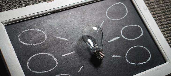 Glühbirne auf schwarzer Tafel und davon wegführend leere Kreidekreise für Ideen